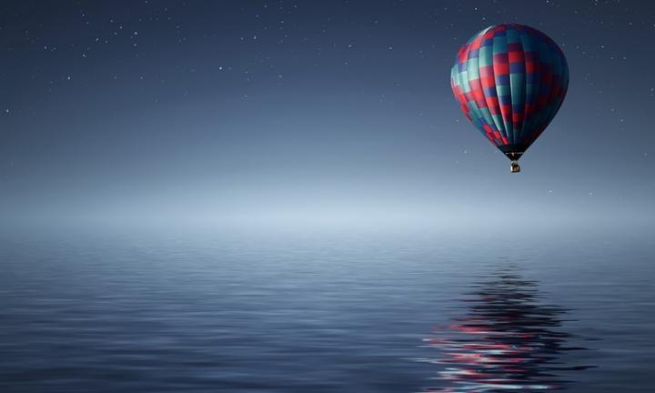 Hot air balloon over water at night